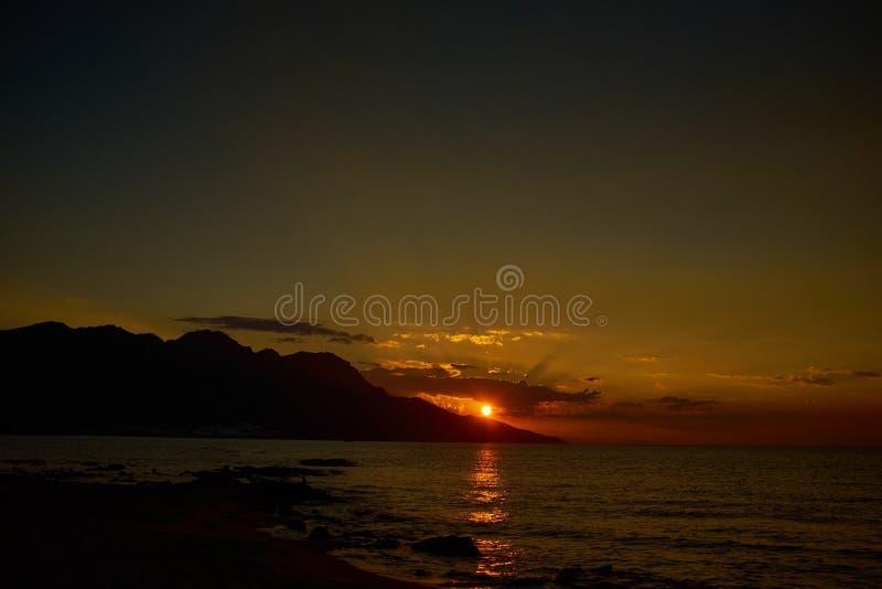 Salida del sol rojo oscuro en un mar fotos de archivo