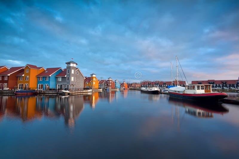 Salida del sol sobre edificios y barcos coloridos en Groninga imágenes de archivo libres de regalías