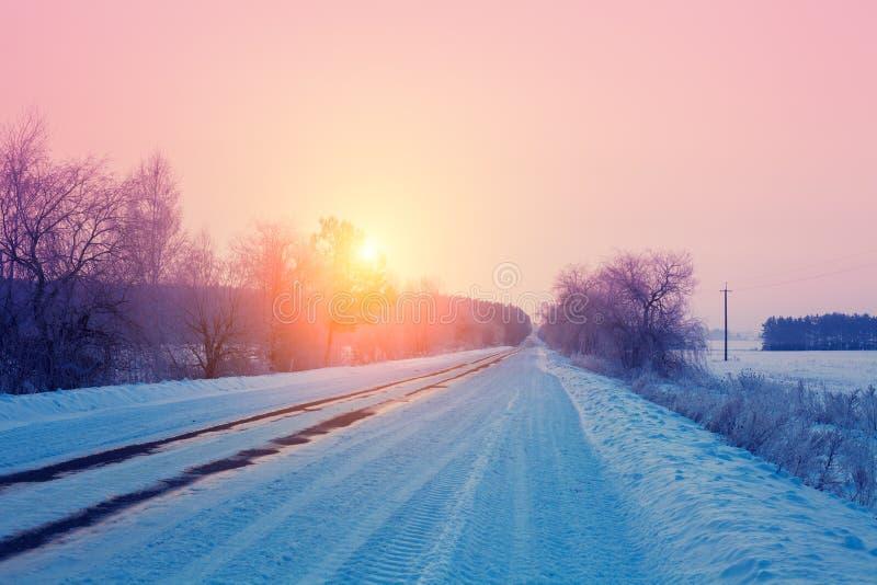 Salida del sol sobre el camino nevoso foto de archivo
