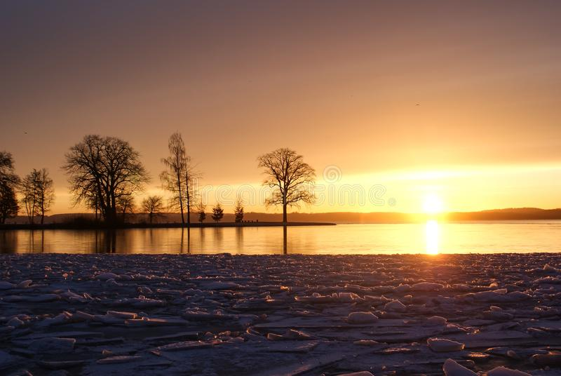 Salida del sol sobre el lago congelado imagen de archivo