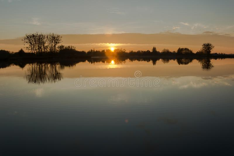 Salida del sol sobre el lago y los árboles en la orilla fotografía de archivo libre de regalías