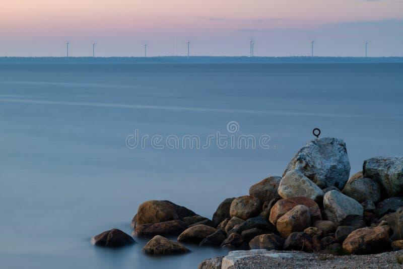 Salida del sol sobre el mar y algunas centrales eléctricas de energía eólica foto de archivo libre de regalías