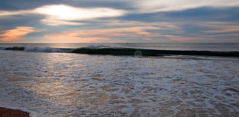 Salida del sol sobre espuma del mar de ondas de fractura en la playa en San Jose Del Cabo en Baja California México fotografía de archivo