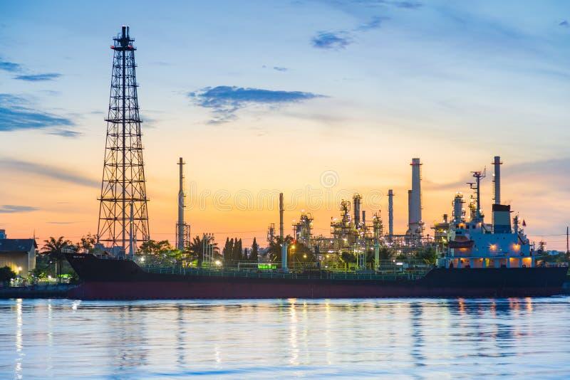 Salida del sol sobre frente del río de la refinería de petróleo foto de archivo