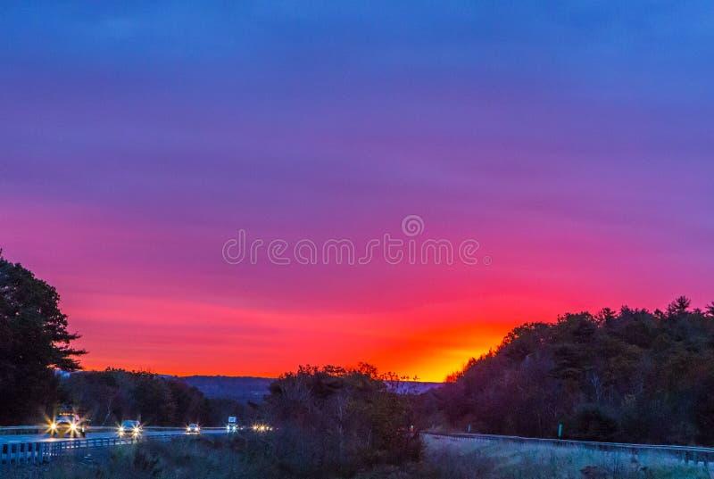 Salida del sol sobre la carretera con colores brillantes fotos de archivo