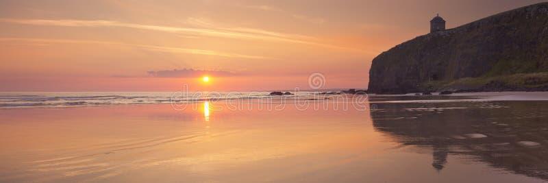 Salida del sol sobre la playa en declive en Irlanda del Norte imagen de archivo