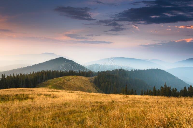Salida del sol sobre picos de la montaña ahumada con la vista del bosque en el primero plano foto de archivo