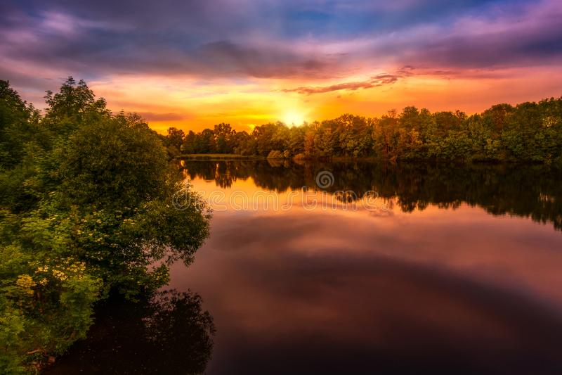 Salida del sol sobre un lago imagen de archivo
