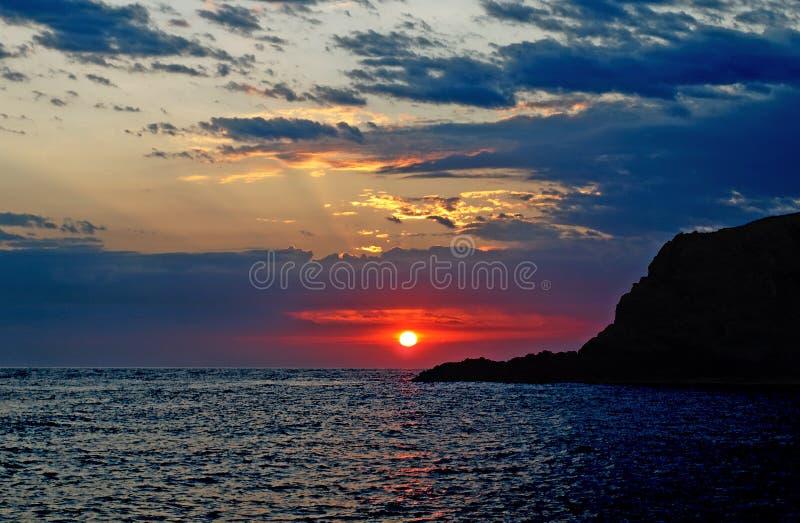 Salida del sol tempestuosa carmesí en el mar imágenes de archivo libres de regalías