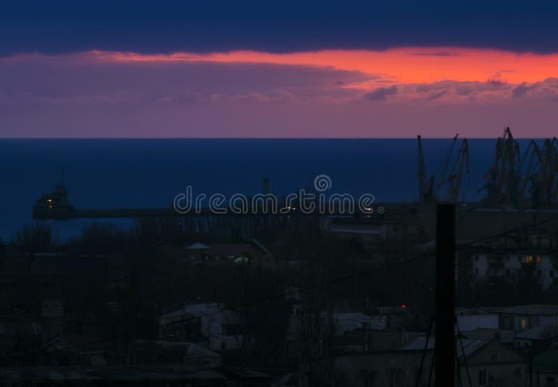 Salida del sol temprana, nubes, litera, ciudad de la mañana y mar imagen de archivo