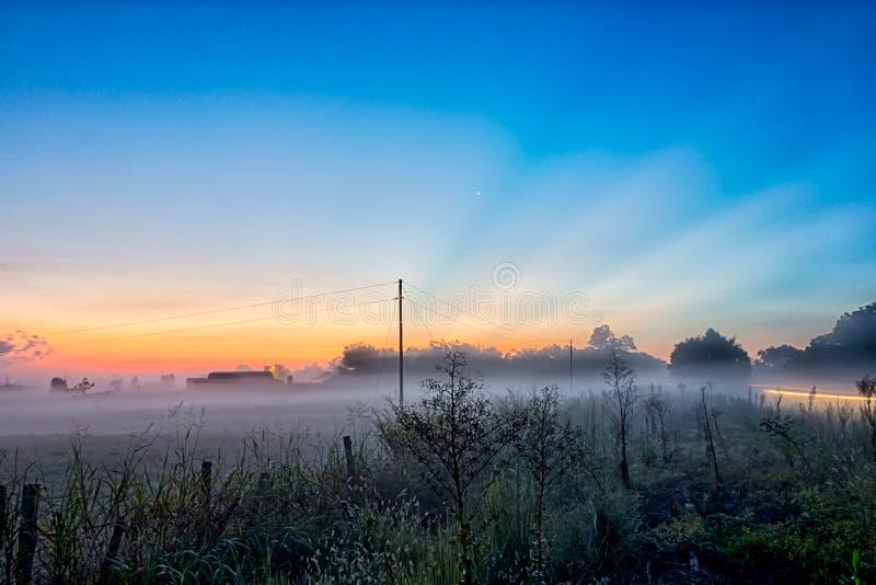 Salida del sol temprana sobre paisaje de niebla de la granja en villancico del sur de la colina de la roca fotos de archivo libres de regalías