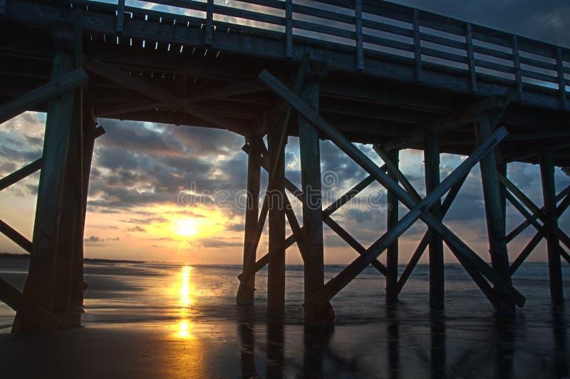 Salida del sol a través de columnas del embarcadero fotos de archivo