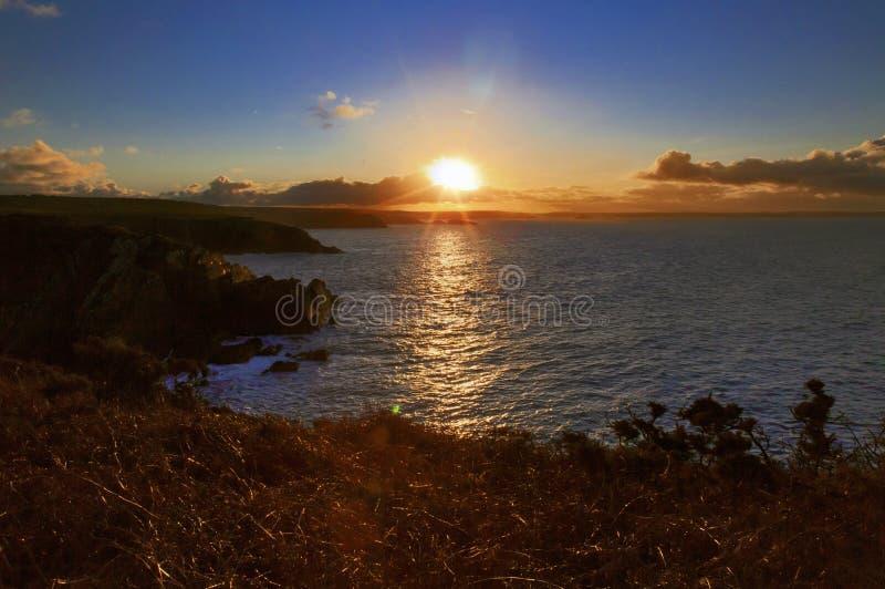 Salida del sol a través de la bahía de las novias del St de Porthclais foto de archivo