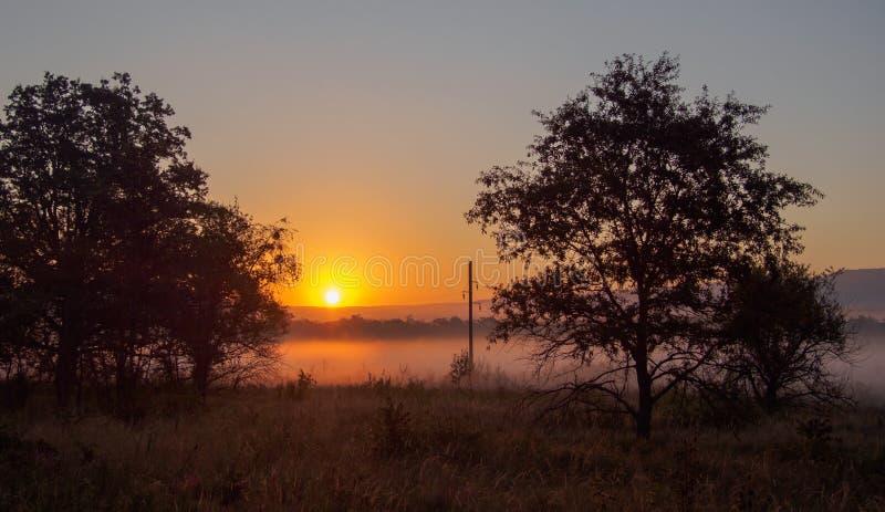 Salida del sol a través de la niebla imagenes de archivo