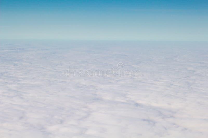 Salida del sol a través de la ventana del aeroplano sobre las nubes fotografía de archivo