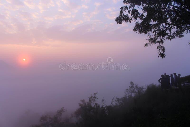 salida del sol a través del mar de la niebla fotos de archivo