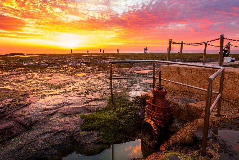 Salida del sol y pescador en Mona Vale Australia foto de archivo libre de regalías