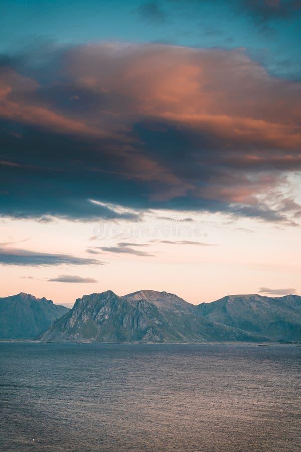 Salida del sol y puesta del sol en Henningsvaer sobre Océano Atlántico con las nubes rosadas El pueblo pesquero situado en varios fotos de archivo