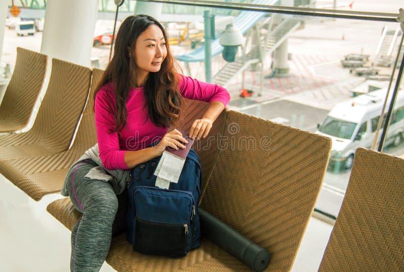 Salida que espera de la muchacha asi?tica feliz joven para en aeropuerto internacional fotografía de archivo libre de regalías