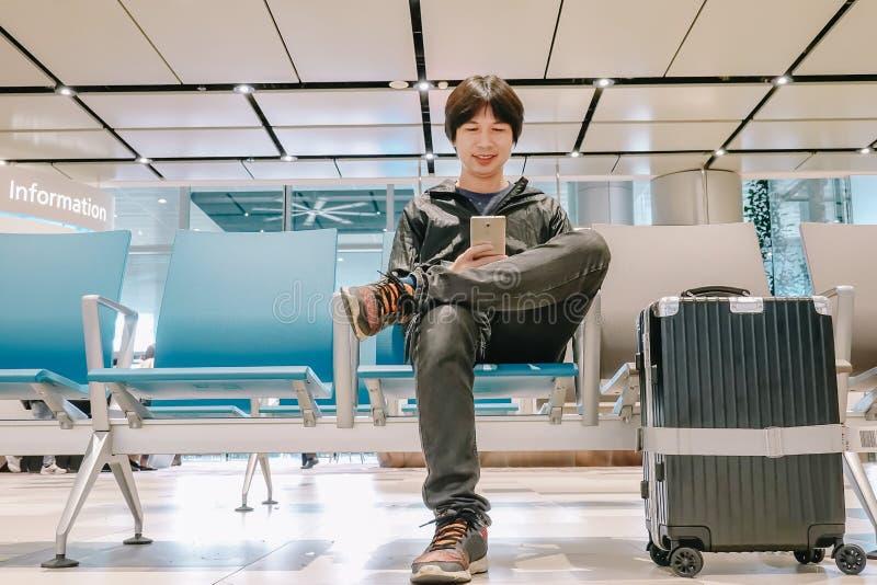 Salida que espera joven del hombre ocupado para en el aeropuerto mientras que usa su teléfono imagen de archivo