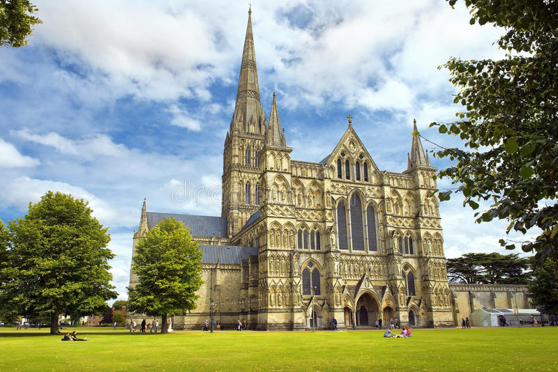 Salisbury Cathedral in England. SALISBURY, UNITED KINGDOM - August 03, 2015: Salisbury Cathedral and park on sunny day on August 03, 2015 in Salisbury, South royalty free stock images