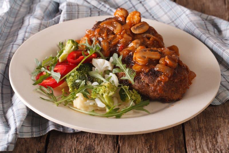 Salisbury steak with mushroom sauce and vegetable salad close-up. On a plate on the table. horizontal stock image