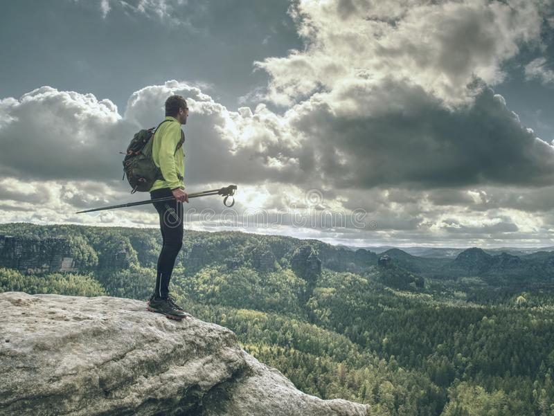 Salita di Skarner sulla montagna con i pali e lo zaino di trekking immagine stock