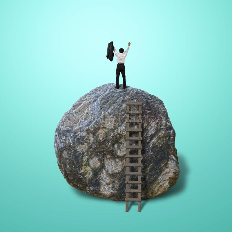 Salita incoraggiata dell'uomo d'affari sopra grande roccia fotografie stock libere da diritti