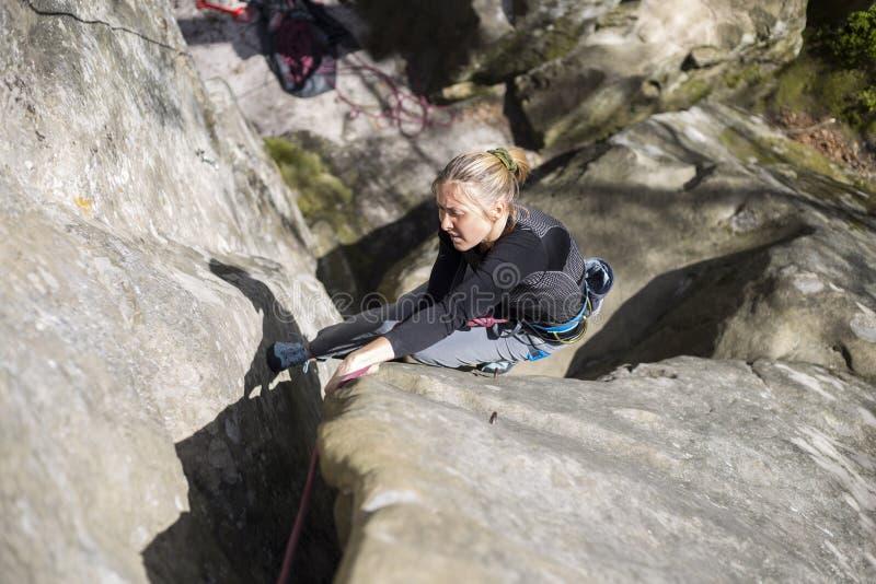 Salite dell'atleta su roccia con la corda immagini stock