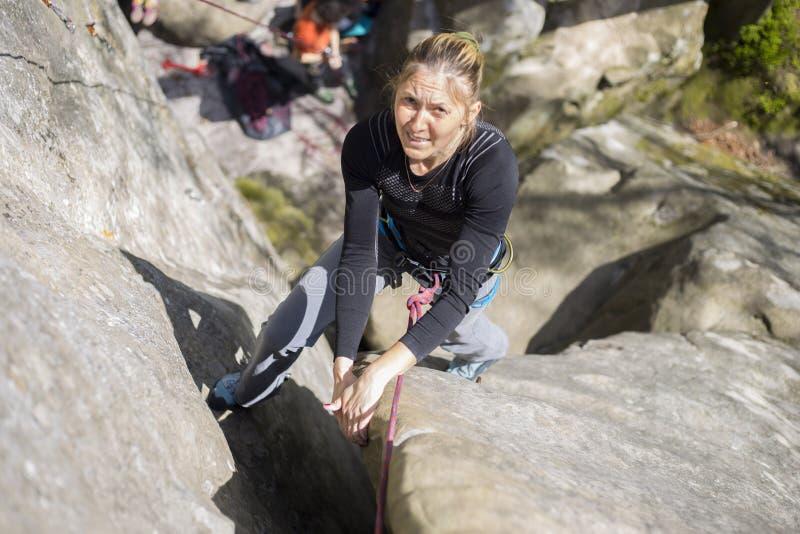Salite dell'atleta su roccia con la corda fotografie stock