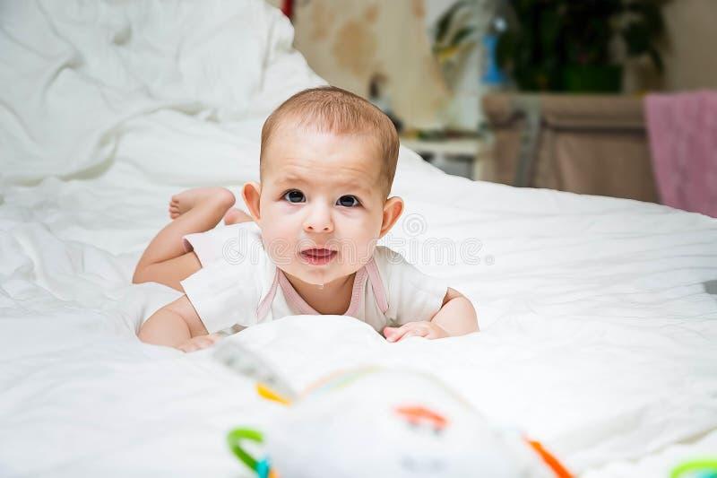 Salivation accrue dans le nourrisson pendant la dentition Un bébé dans des vêtements blancs se trouve sur un lit blanc, souriant, photographie stock