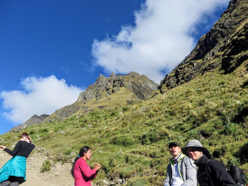 A young group of international hikers, led by their local Inca guide, navigate the Andes mountains on the Salkantay Trail royalty free stock photo