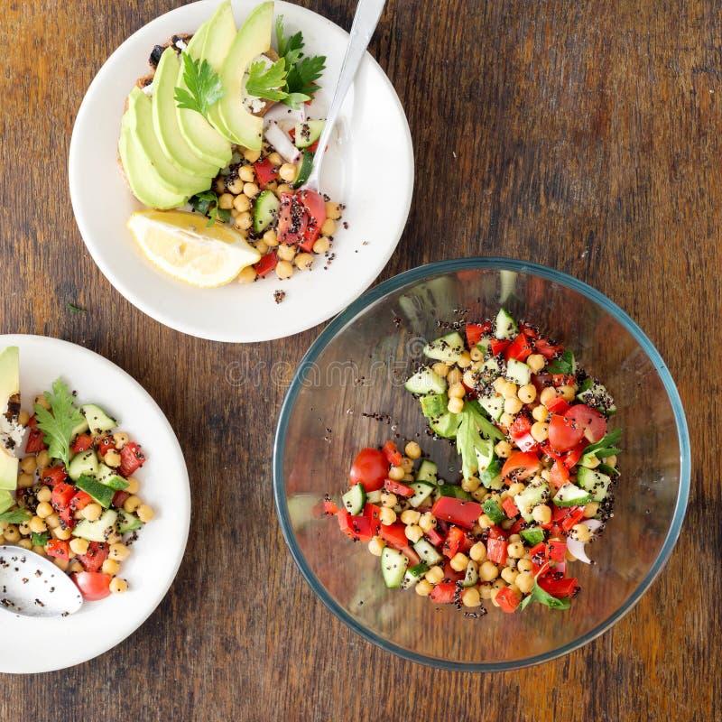 Sallad av den svarta quinoaen, kikärtar och grönsaker med avokadobru royaltyfri bild