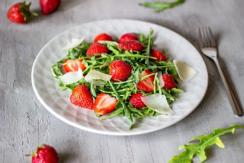 Sallad av jordgubbar, arugula och ost p? en gr? bakgrund dietary mat royaltyfria bilder