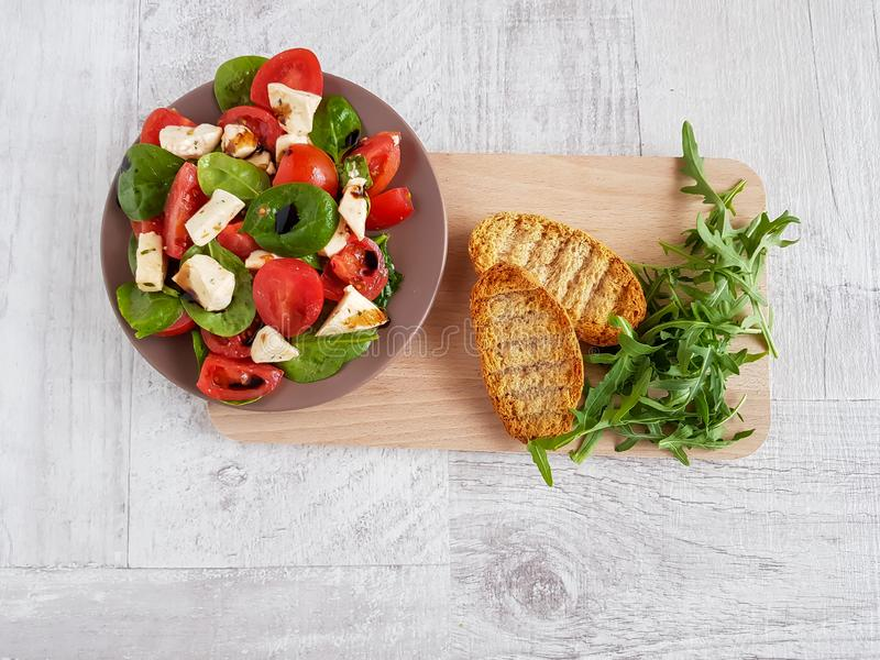 Sallad av körsbärsröda tomater, spenat, mozzarellastycken med basilika som kryddas med olivolja och balsamic vinäger fotografering för bildbyråer