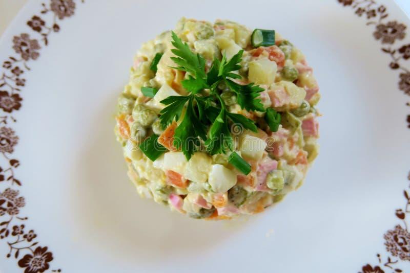 Sallad av kokta grönsaker, ägg, skinka och persilja på en vit plattanärbild arkivfoton