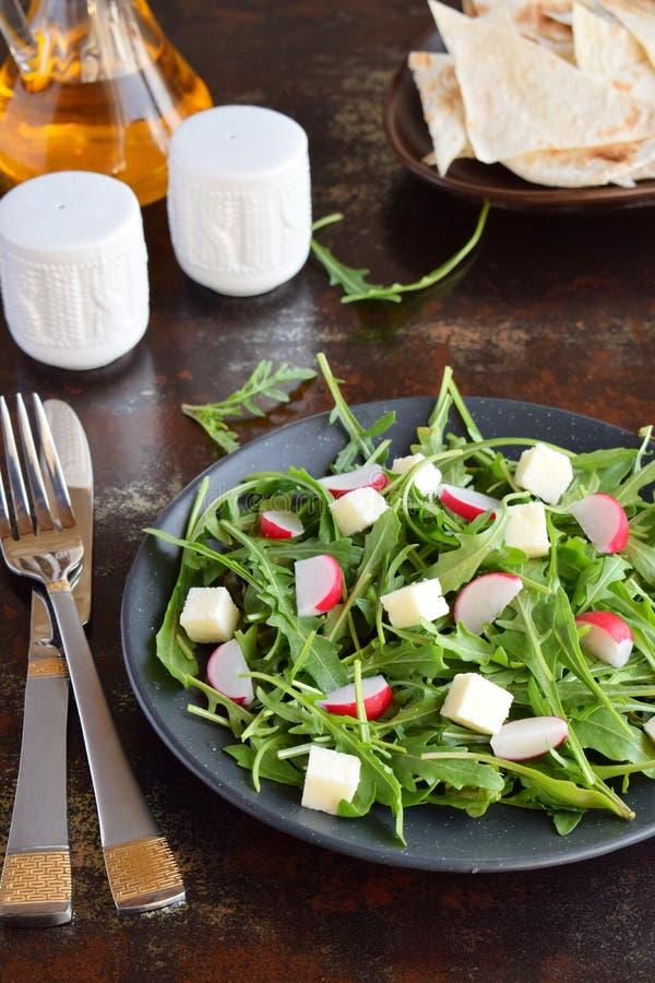 Sallad av nya gr?nsaker - arugula, r?disa, fetaost i svart platta med den plana br?dtortillan sund mat royaltyfri bild