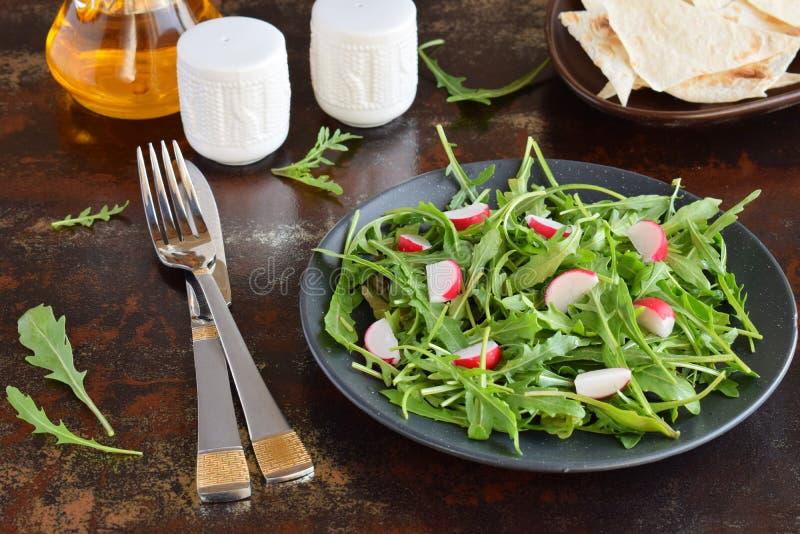 Sallad av nya gr?nsaker - arugula, r?disa, fetaost i svart platta med den plana br?dtortillan sund mat royaltyfri foto
