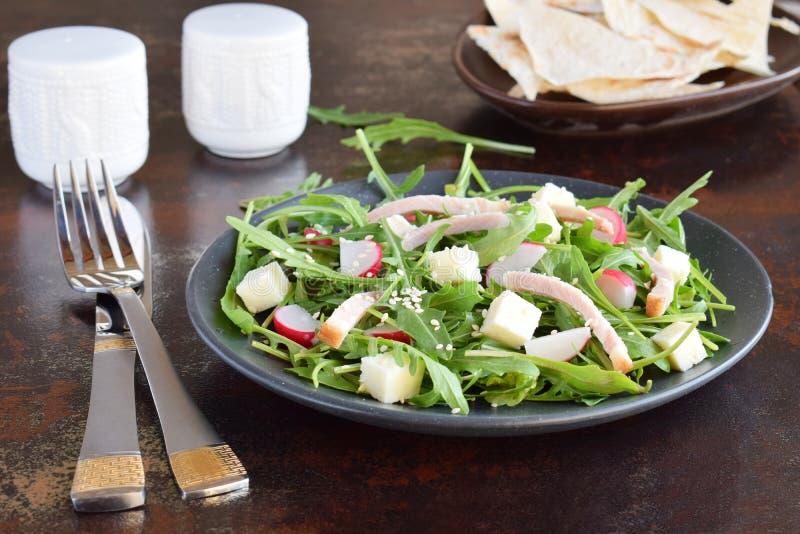 Sallad av nya gr?nsaker - arugula, r?disa, fetaost i svart platta med den plana br?dtortillan sund mat arkivfoton