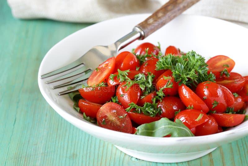 Sallad av små körsbärsröda tomater med persilja royaltyfri foto