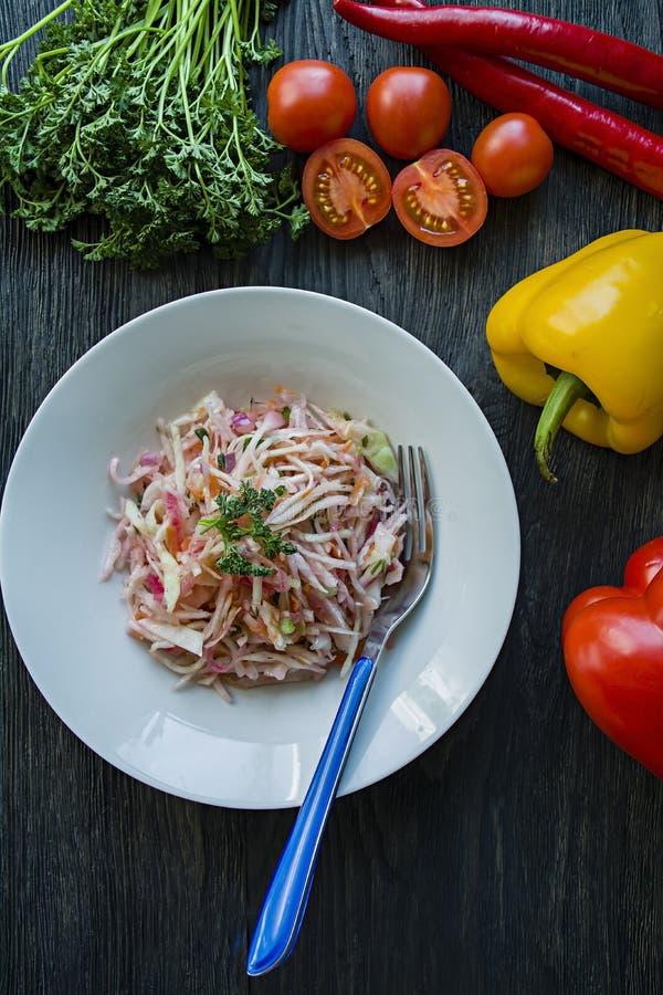 Sallad av vit k?l, mor?tter och spanska peppar dekorerat med gr?splaner och gr?nsaker b?nagurkor besegrar nya stekte vegetariska  arkivfoton