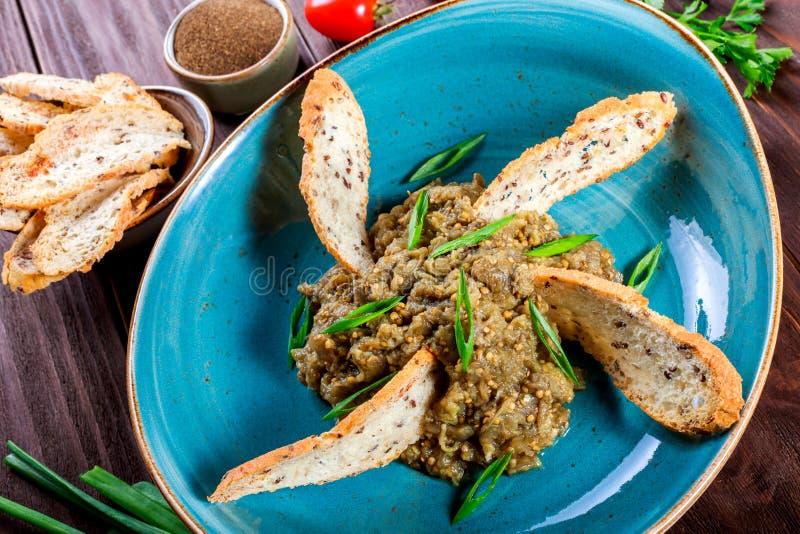 Sallad bakade aubergine med salladslökar, vitlök, örter, krutonger och tomater på mörk träbakgrund Ingredienser på tabellen royaltyfri foto