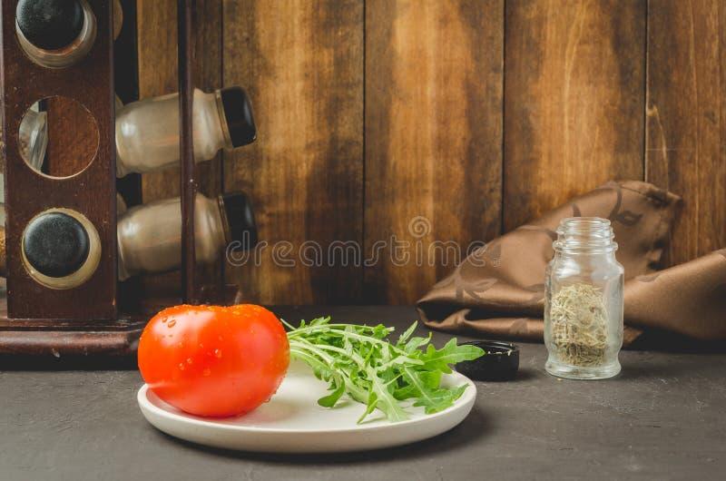 Sallad Den skivade tomaten med arugula i en vit bunke, med kryddor mot en mörk bakgrund royaltyfri bild
