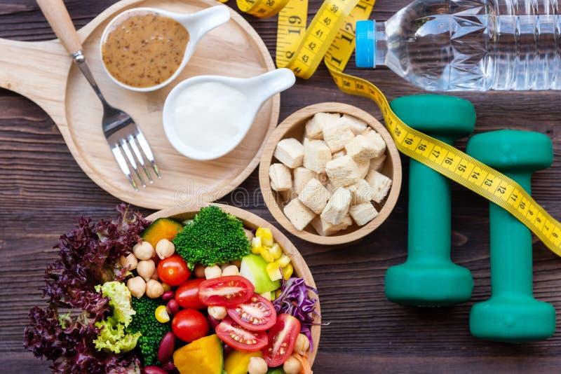 Sallad för den nya grönsaken och sund mat för sportutrustning för kvinnor bantar att banta med måttklappet för viktförlust på trä royaltyfria bilder