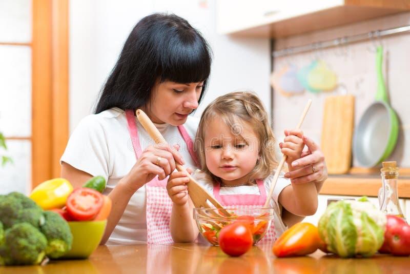 Sallad för dotter för moderundervisningunge blandande på kök fotografering för bildbyråer