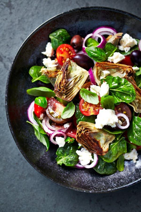 Sallad för körsbärsröd tomat och spenatmed kronärtskockahjärtor, kalamata oliv och fetaost Medelhavs- kokkonst Den nya och saftig arkivbilder