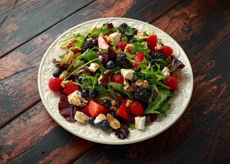 Sallad för ny frukt med blåbäret, jordgubbehallonet, valnötter, fetaost och gröna grönsaker Sund sommarmat royaltyfria bilder