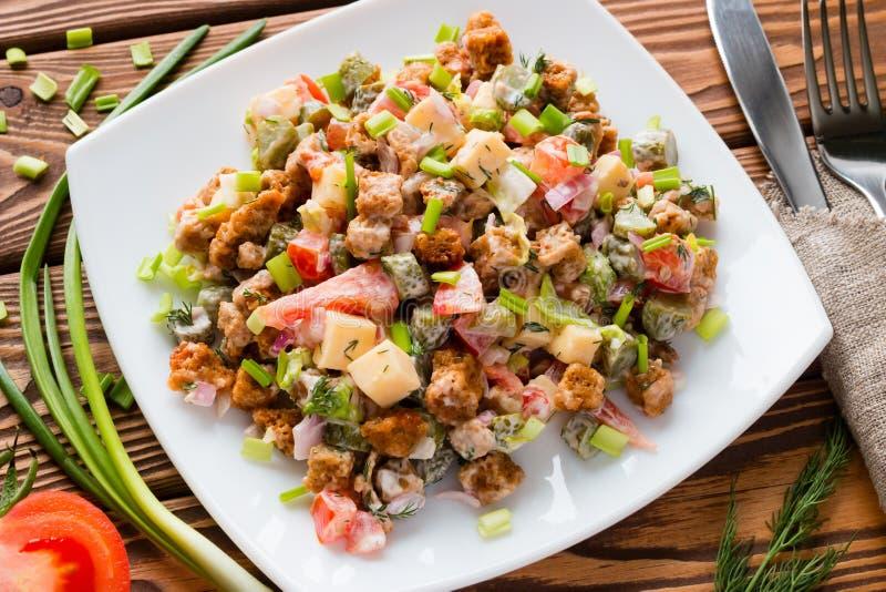 Sallad för ny grönsak i en vit platta med salladslöken och tomaten på en tabell royaltyfri fotografi