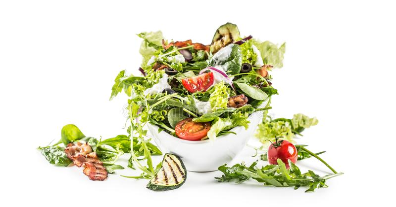 Sallad för ny grönsak med den stekte dressingen och olivolja för tzatziki för zucchini för arugula för bacontomatoliv som isolera arkivbild