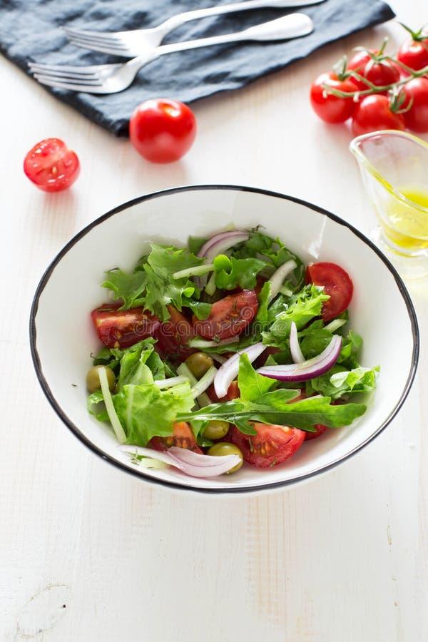Sallad för ny grönsak med gräsplaner, tomater, oliv och lökar royaltyfria bilder